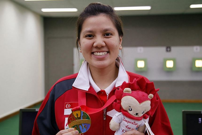 Singapore shooter Teo Shun Xie holding up her SEA Games gold medal in the women's individual 10m air pistol event on June 7, 2015. -- PHOTO: SINGAPORE SEA GAMES ORGANISING COMMITTEE/ACTION IMAGES VIA REUTERS
