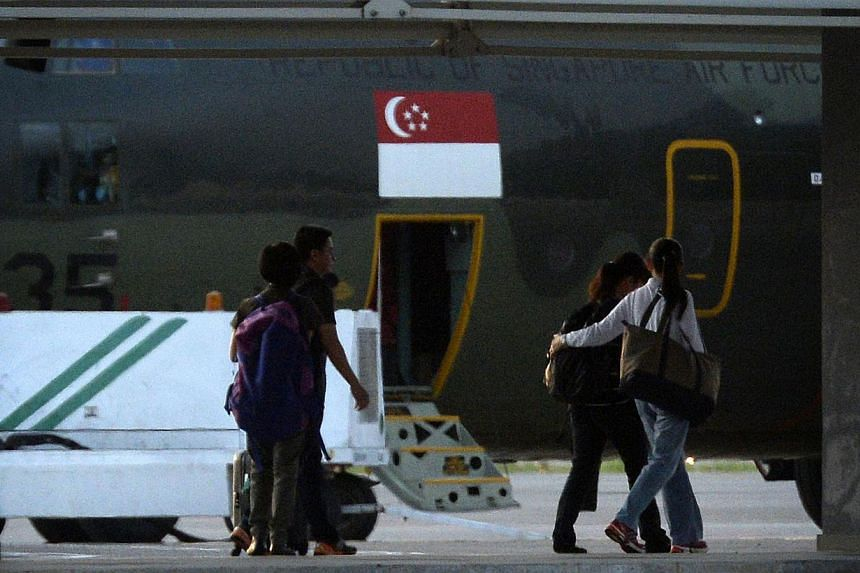 Families of the deceased and other personnel, ushered by staff members from the Ministry of Foreign Affairs, preparing to board a Singapore Armed Forces airplane headed for Singapore at the Kota Kinabalu airport on June 7, 2015. -- ST PHOTO: MARK CHE