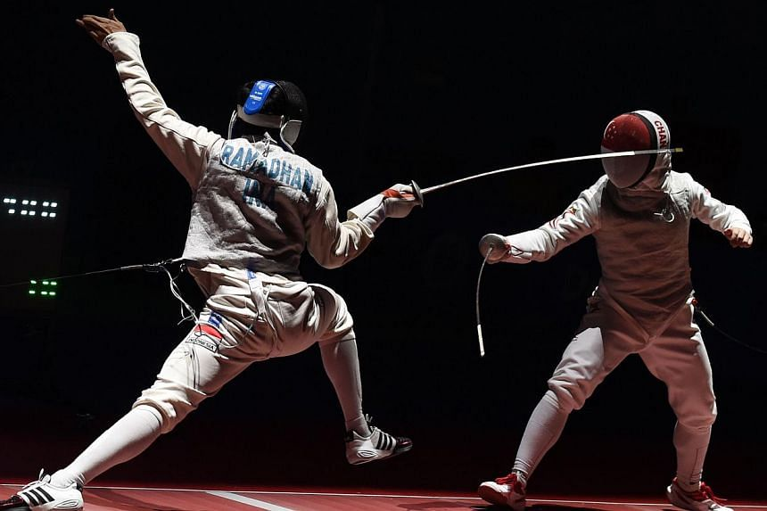 Kevin Jerrold Chan (right) of Singapore competes against Tauhid Ramadhan (left) of Indonesia during the 28th SEA Games held in Singapore on June 7, 2015. -- PHOTO: AFP