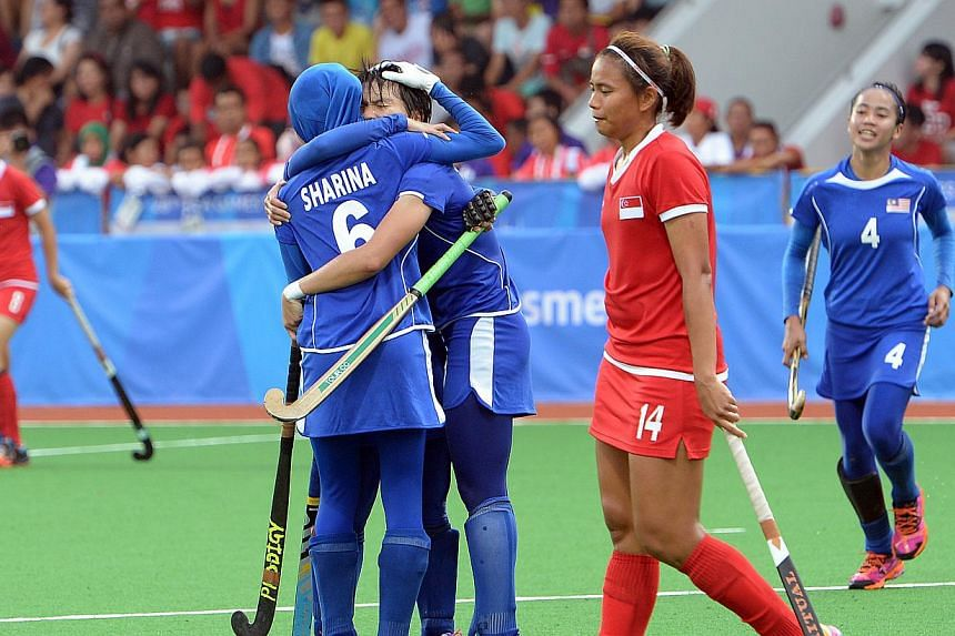 Singapore's Toh Limin walking past her jubilant Malaysian opponents after the women's hockey team was hammered 7-0 in their SEA Games opener at Sengkang hockey stadium on June 6, 2015. -- ST PHOTO: DESMOND WEE
