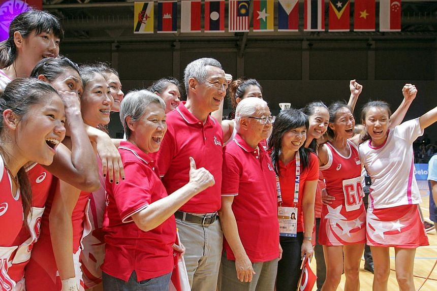 (From left) Ho Ching, Prime Minister Lee Hsien Loong and President Tony Tan Keng Yam posing for a photo with Singapore's netballers after their historic gold medal. -- ST PHOTO: SEAH KWANG PENG