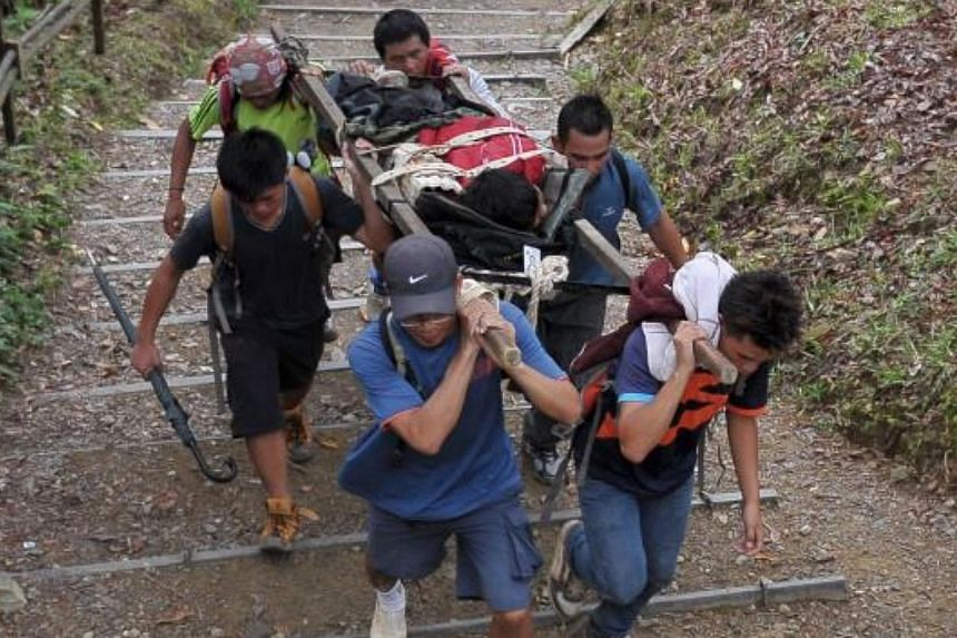 Sabahan mountain guides carrying an injured climber. -- PHOTO: THE STAR/ASIA NEWS NETWORK