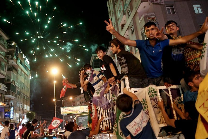 Supporters of the Peoples' Democratic Party (HDP) drive in a car convoys and launch firework in the streets as they celebrate the results of the Turkish parliamentary elections, in Diyarbakir, Turkey, on June 8, 2015. -- PHOTO: EPA