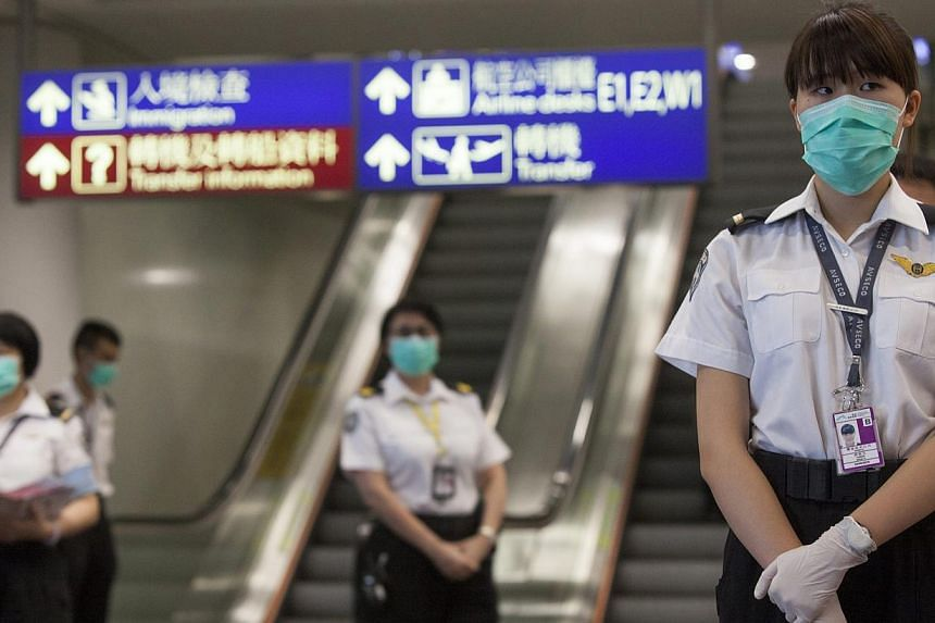 Health workers from Hong Kong's Department of Health are seen prior to checking passengers arriving for Middle East Respiratory Syndrome (MERS), at Hong Kong International Airport, Hong Kong, China, on June 5, 2015. -- PHOTO: EPA