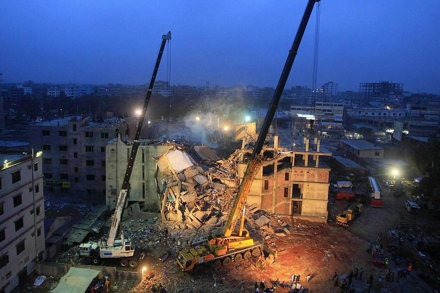 In this photograph taken on April 29, 2013, cranes operated by Bangladeshi Army personnel are pictured at the scene following the April 24 collapse of an eight-storey building in Savar, on the outskirts of Dhaka. -- PHOTO: AFP