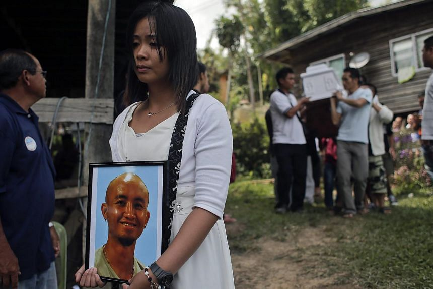 Jessica Sikta (second from left) holds a picture of her fiance Valerian Joannes, a 27-year-old tour guide who was among those killed in an earthquake which hit Sabah, during his funeral ceremony in Kundasang, Sabah, Malaysia, on June 8, 2015. -- PHOT