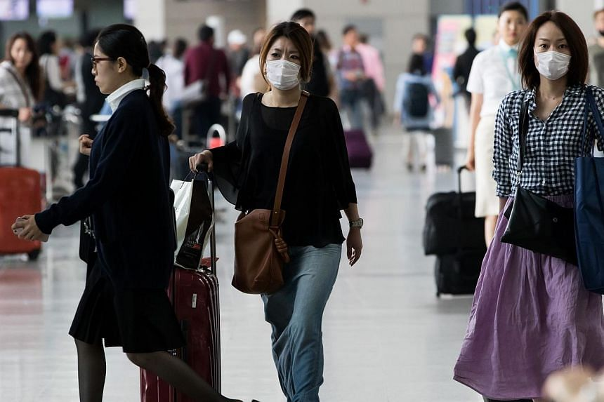 Tourists wearing face masks walk through Incheon International Airport in Incheon, South Korea, on Monday, June 8, 2015.To detect Mers-CoV cases early, Singapore will start temperature screening at air checkpoints for passengers arriving from S
