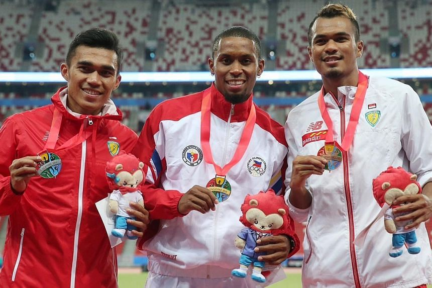 (From left) Indonesia's Yaspi Boby (silver), Philippines' Eric Shauwn Cray (gold) and Indonesia's Iswandi (bronze) on the podium after the men's 100m final at the National Stadium on June 9, 2015. -- ST PHOTO: NEO XIAOBIN