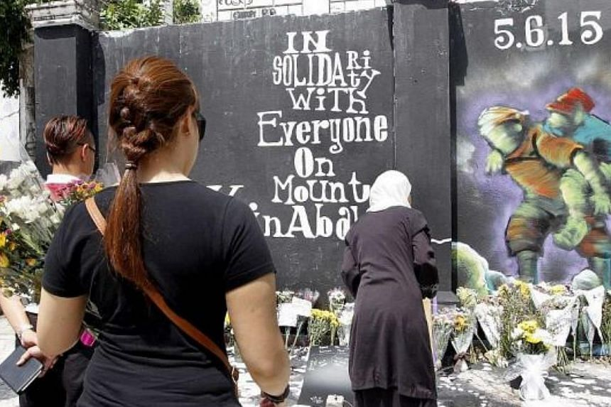 People paying their last respects to the victims of the earthquake at Mount Kinabalu at the graffiti corner of the old ruined colonial building in Kota Kinabalu. -- PHOTO: THE STAR/ASIA NEWS NETWORK