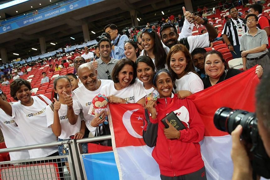 Singapore's Shanti Pereira (in red) posing with her family and friends after her bronze medal win. -- ST PHOTO: NEO XIAOBIN