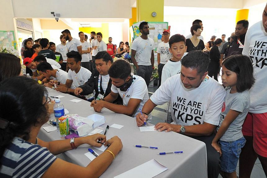 Young Lions team coach Aide Iskandar (right, seated) writes his condolences during the team's visit to Tanjong Katong Primary School. -- PHOTO: LIM YAOHUI FOR THE STRAITS TIMES