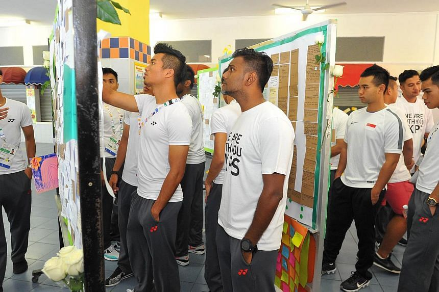 Some members of The Young Lions team penning their tributes on the condolence board. -- PHOTO: LIM YAOHUI FOR THE STRAITS TIMES