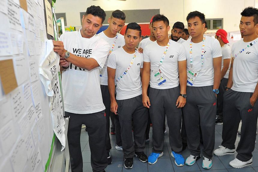 "Young Lions team coach Aide Iskandar (left) pinning a white shirt with the words, ""We are with you TKPS"" onto one of the condolence boards. -- PHOTO: LIM YAOHUI FOR THE STRAITS TIMES"