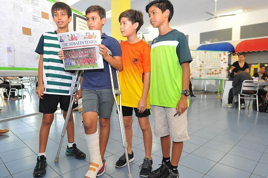 (From left) Chaityak Khatwani, 12, Jayden Francis, 12, So Kwan Wing Tristan Jun, 12 and Muhammed Khaleil, 11, showing a copy of The Straits Times that was signed by members of the Young Lions team. -- PHOTO: LIM YAOHUI FOR THE STR