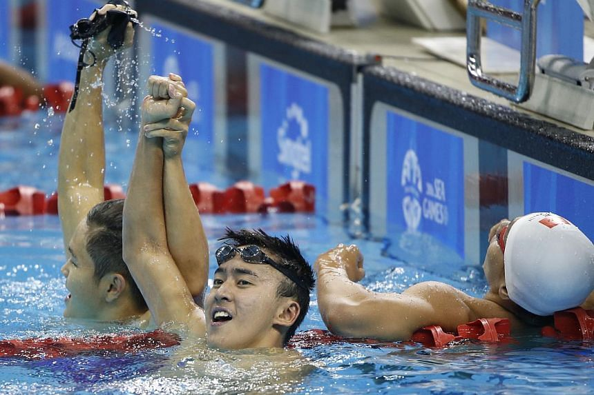 Swimmer Quah Zheng Wen (centre) raising his right hand in triumph with teammate Pang Sheng Jun (left) after winning the 400m individual medley on June 9, 2015. It was Singapore's 51st gold medal of the SEA Games, breaking the previous mark of 50 set