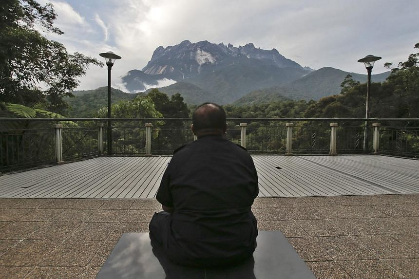 A policeman sits facing the Kinabalu Mountain as a rescue mission continues for climbers stranded on one of Southeast Asia's highest mountains after an earthquake, Sabah, in Kundasang, Malaysia, June 6, 2015. -- PHOTO: EPA