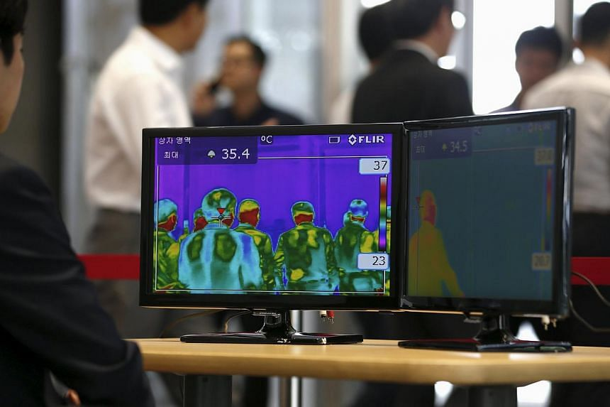 Employees walking past a thermal imaging camera at an office buliding in central Seoul, South Korea, on June 9, 2015, as fears over an outbreak of Middle East respiratory syndrome (Mers)grips the country.The Philippines has had close brus