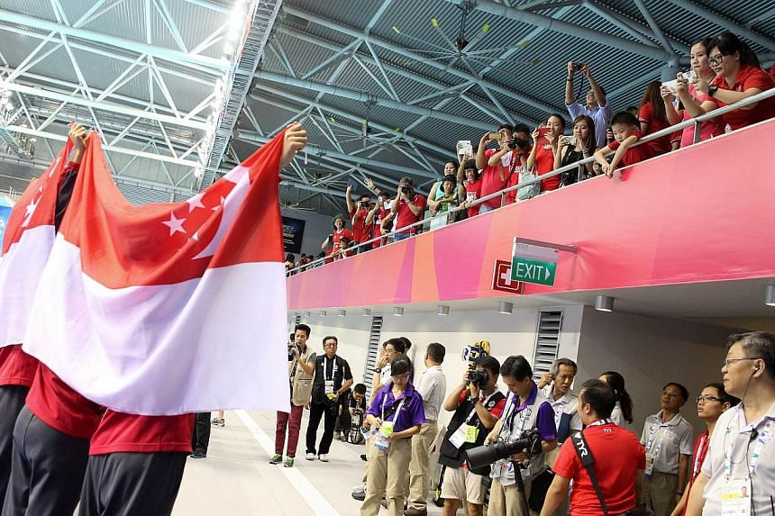 The women's 4x200m freestyle relay quartet of Quah Ting Wen, Amanda Lim, Rachel Tseng and Christie Chue acknowledging the crowd at the OCBC Aquatic Centre after their win.-- ST PHOTO:ONG WEE JIN