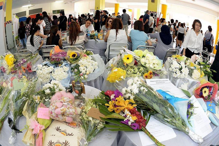 Bouquets of flowers that were left by hundreds of parents, pupils, alumni and staff at a condolence site in the school porch of Tanjong Katong Primary School on June 8, 2015. -- ST PHOTO: DESMOND WEE