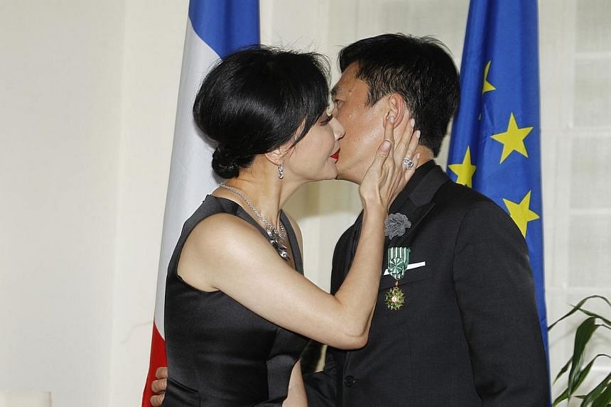 Carina Lau kisses Tony Leung after he was made an Officer of the Order of Arts and Letters by France's consul general Arnaud Barthelemy. -- PHOTO: APPLEDAILY