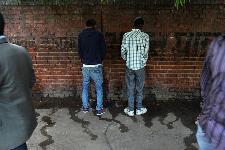 In this photograph taken on Nov 18, 2014, Indian men urinate on a wall at the roadside in New Delhi, the eve of World Toilet Day. A city council in western India is planning to pay residents to use public toilets in a desperate attempt to stop legion