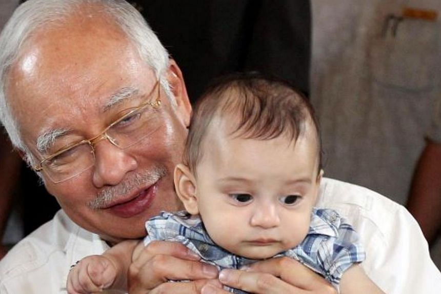Datuk Seri Najib Tun Razak holding Camaron Robbi, son of the late Robbi Sapinggi, during a visit to Mount Kinabalu. -- PHOTO: THE STAR/ ASIA NEWS NETWORK