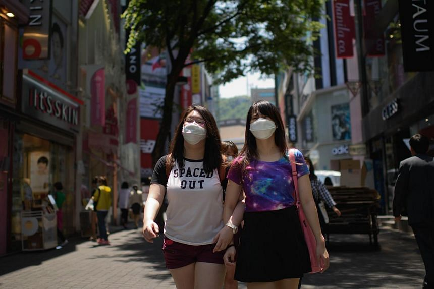 Tourists wearing face masks walk in the popular Myeongdong shopping area in Seoul on June 4, 2015.Taiwanese health authorities issued a travel alert to cover all of South Korea late on Tuesday, widening its caution on travel to the country stri
