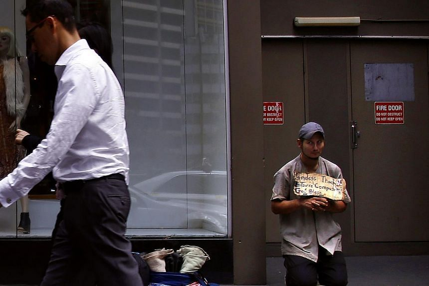 A pedestrian walks past a man holding a sign as he begs for money on a main street in central Sydney on March 18, 2015. Australian unemployment unexpectedly fell in May to the lowest in a year, indicating that improved business confidence is translat