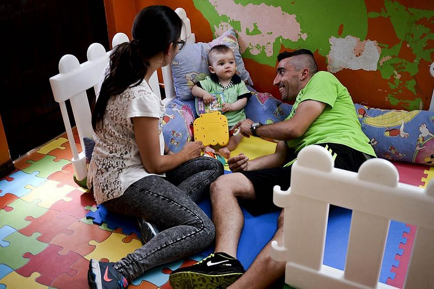 A file picture taken on May 14, 2015 shows Jessica (left) and her husband Antonio (right) playing with their child Martim born on August 8, 2014 at the kindergarten in Alcoutim, southern Portugal. The mayor of the small town of Alcoutim, in southern