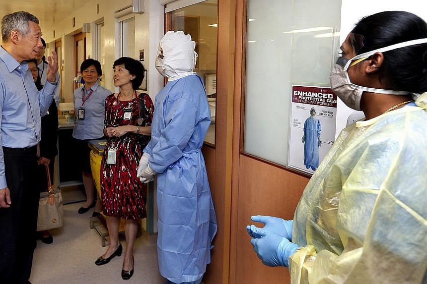 (From left) Prime Minister Lee Hsien Loong with senior consultant Brenda Ang, and nurses Felicia Tang and Sujithra Nair at Tan Tock Seng Hospital, which is Singapore's designated isolation centre for suspected and confirmed Mers patients. -- ST PHOTO
