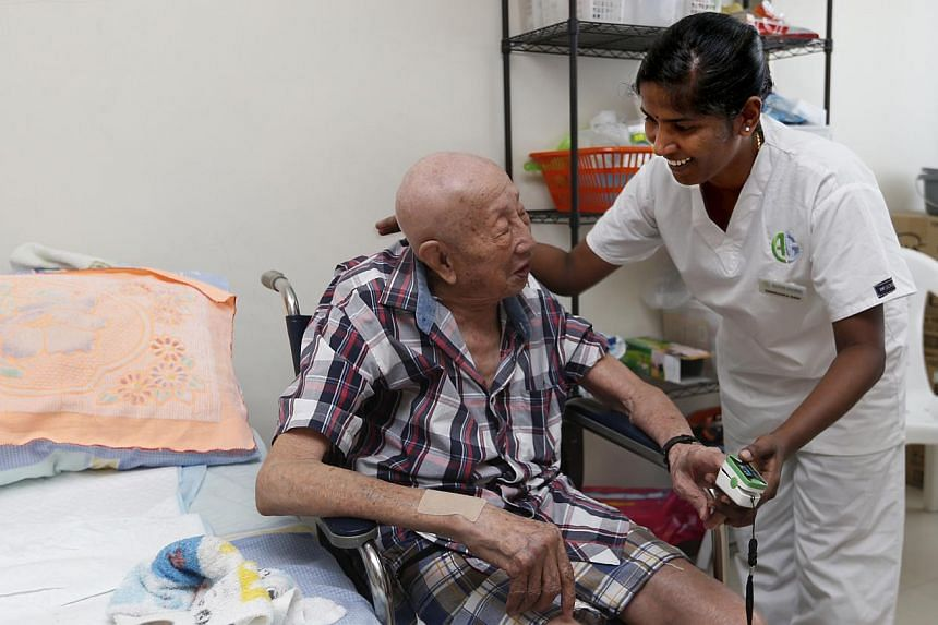 Ms Swaroopa Rani, a nurse from India, takes care of Mr Goh Chong Huat at his home near Bedok. He used to be in and out of hospital every month, but has not had to be hospitalised since Ms Rani started caring for him.