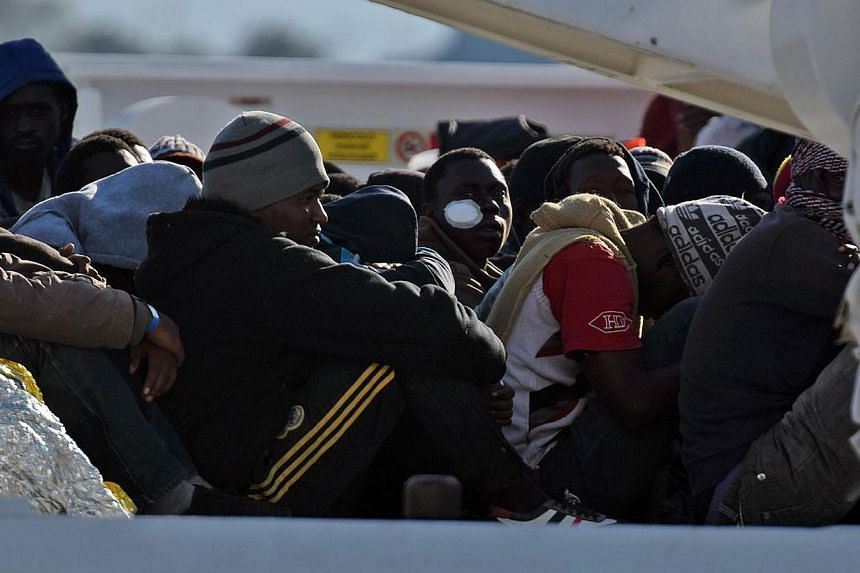 Shipwrecked migrants sitting on the deck of a rescue vessel as they arrived in the Italian port of Augusta in Sicily in April. A market in which states can buy and sell all or part of their protection quota obligations should be created, suggests the