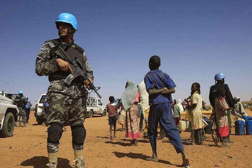 Sudanese people walk past members of the UN-African Union mission in Darfur (Unamid) at the Zam Zam camp for Internally Displaced People (IDP), North Darfur, on April 9, 2015. The UNon Wednesday, June 10, warned that violent attacks on internat