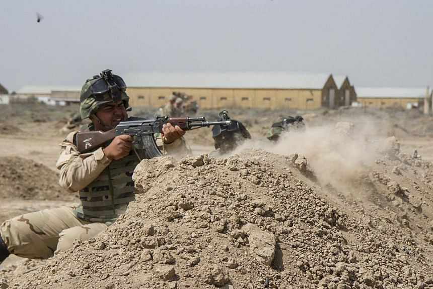 Iraqi soldiers train with members of the US Army 3rd Brigade Combat Team, 82nd Airborne Division, at Camp Taji, Iraq, on June 2, 2015. US President Barack Obama on Wednesday, June 10, approved the deployment of up to 450 more US military personn