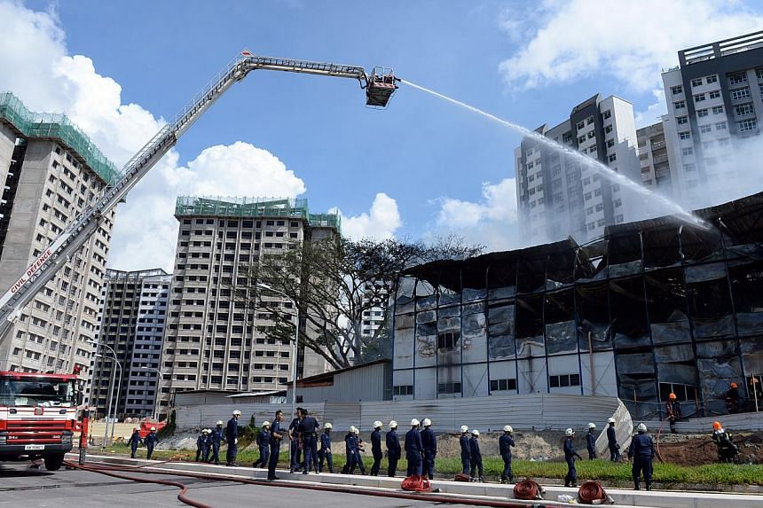 SCDF putting out the fire at a construction site for a Build-to-Order estate at Keat Hong Link Road. -- ST PHOTO: DESMOND FOO