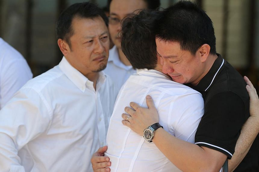Father of Rachel Ho being comforted by family and friends. -- ST PHOTO: ONG WEE JIN