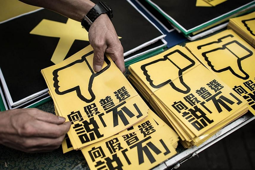 In this picture taken on April 26, 2015 in Hong Kong, a pan-democrat arranges leaflets against the government's controversial leadership election roadmap which sticks to a ruling from Beijing that all candidates should be vetted before a public vote