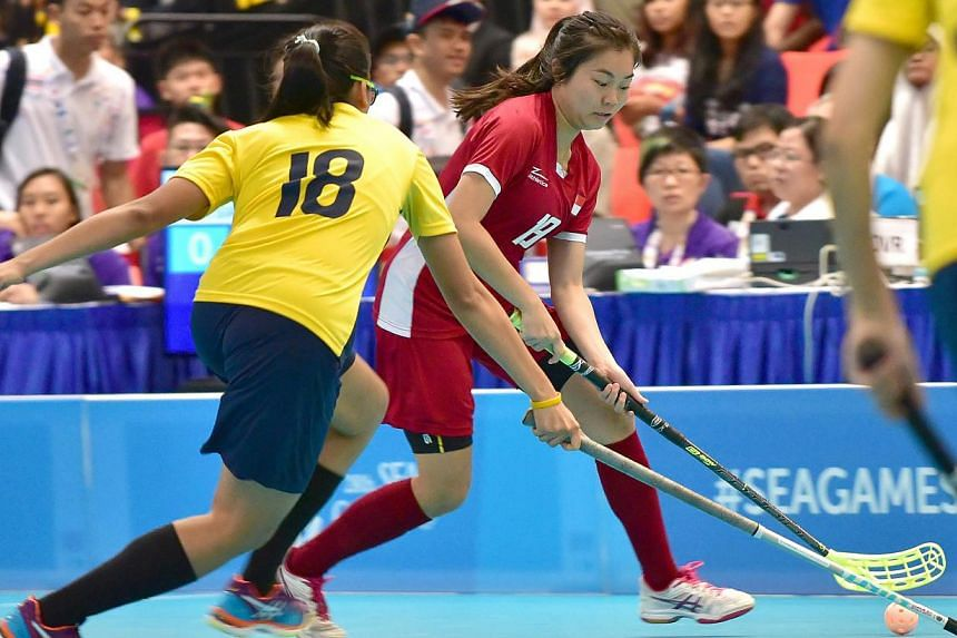 Singapore and Malaysia women's floorball teams in action at ITE College Central on June 11, 2015. Singapore's floorball teams are off to a flying start on the opening day of the SEA Games competition on Thursday, with both men and women chalking up b