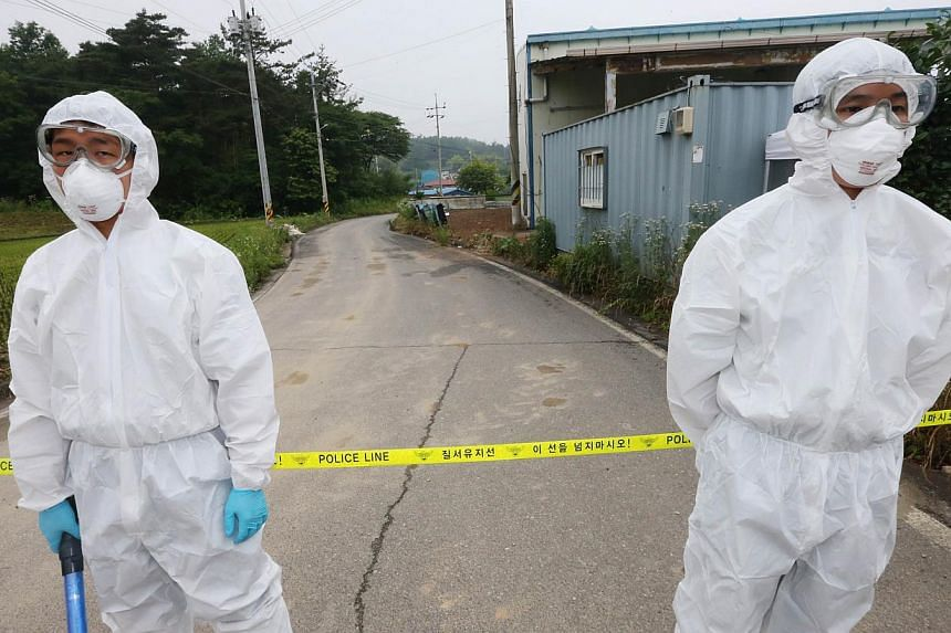 Health workers wearing protective suits stand by the cordon of a quarantined village in Boseong, at the tip of the South Korean peninsula on June 11, 2015. A South Korean man with terminal lung cancer who had been infected with the Middle East Respir