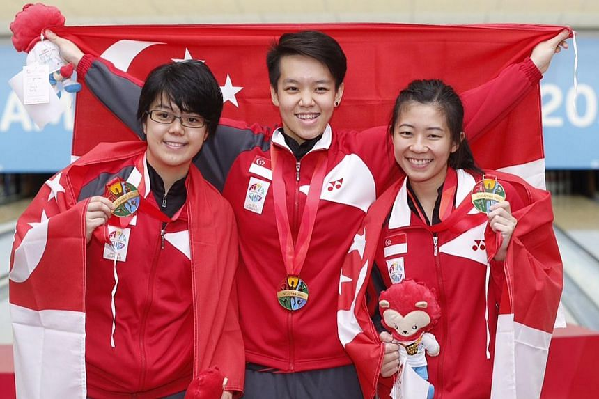 Singapore's (from left) Cherie Tan, Shayna Ng and Bernice Lim with gold medals from the women's trios event during the 28th SEA Games at Orchid Country Club on June 11, 2015. -- ST PHOTO: KEVIN LIM