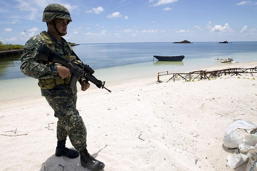 A Filipino soldier patrols the shore of Pagasa island (Thitu Island) in the Spratly group of islands in the South China Sea, west of Palawan, Philippines, in this May 11, 2015 file photo. -- PHOTO: REUTERS