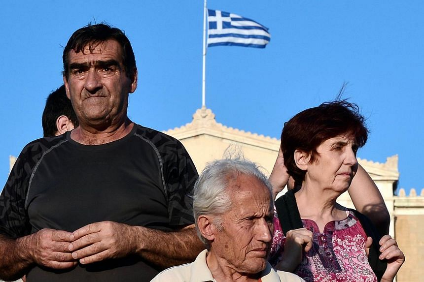 Protesters stand in front of the Greek parliament in central Athens during a rally against the EU-IMF loan deal on June 11, 2015. Greece's creditors piled pressure on cash-strapped Athens on Thursday as the IMF pulled its team out of talks and the EU