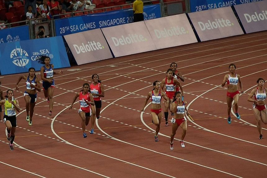 Singapore's Shanti Pereira handing the baton to teammate Smriti Menon in the women's 4x100m relay on June 12, 2015. The team lost out on a bronze by 0.007 seconds. -- ST PHOTO: NEO XIAOBIN