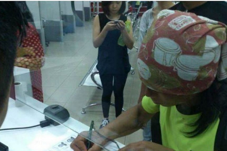 Rizuan signing documents at the Immigration office. -- PHOTO: THE STAR/ASIA NEWS NETWORK