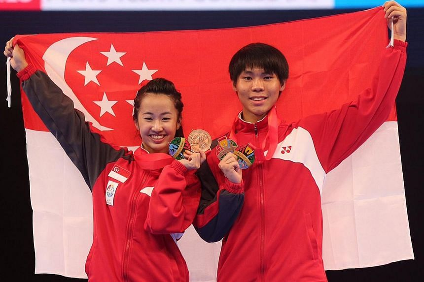 Singapore's Chelsea Sim (left) and Kang Rui Jie with their bronze medals in the mixed poomsae event at the Singapore Expo Hall 2 on June 12, 2015. The pair had earlier won golds in their respective individual poomsae events. -- ST PHOTO: NEO XIAOBIN&