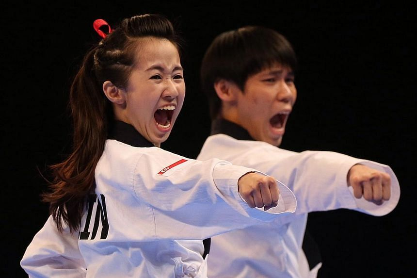 Chelsea Sim and Kang Rui Jie competing in the mixed poomsae event held at the Singapore Expo Hall 2 on June 12, 2015.-- ST PHOTO: NEO XIAOBIN