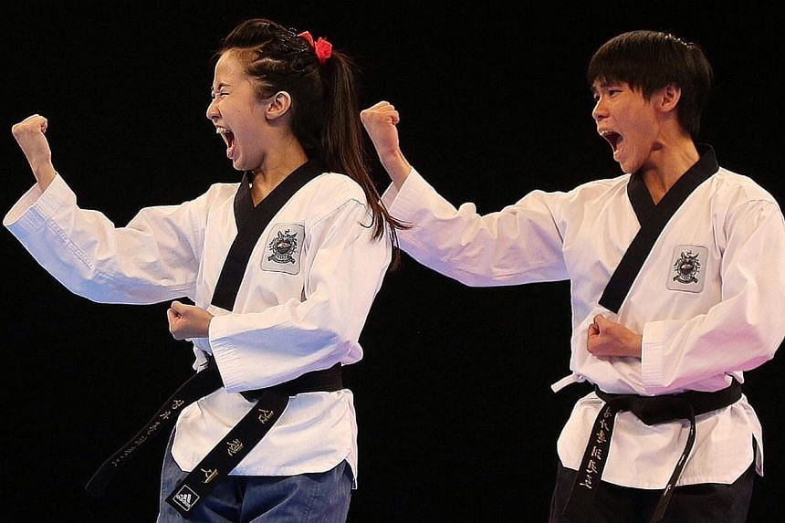 Chelsea Sim and Kang Rui Jie competing in the mixed poomsae event held at the Singapore Expo Hall 2 on June 12, 2015. -- ST PHOTO: NEO XIAOBIN