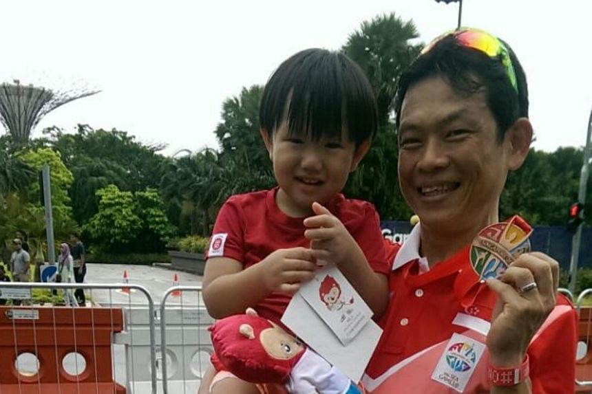 Singapore cyclist Vincent Ang, carrying his son Joshua, with his SEA Games bronze medal in the men's criterium on June 12, 2015. -- ST PHOTO: HO SI RUI