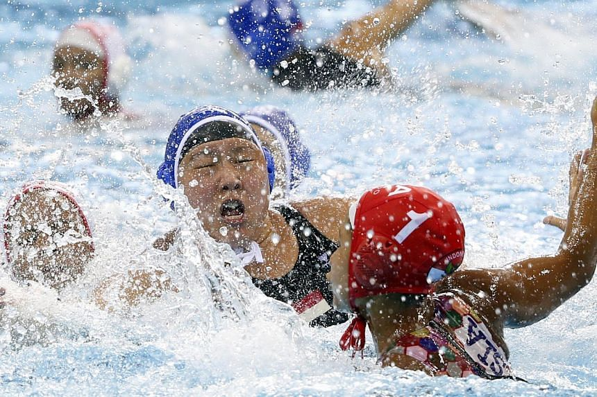 Singapore's Adelyn Yew (blue cap) tussling with Indonesia's Ayudya Suidarwanty Pratiwi (right) during their women's water polo opener on June 10, 2015. -- ST PHOTO: KEVIN LIM