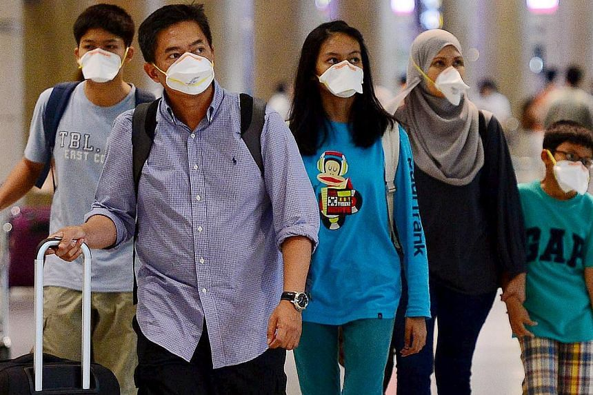 Tourists wearing masks to prevent themselves from contracting Middle East Respiratory Syndrome (Mers) arrive at the Incheon International Airport in South Korea on June 7, 2015. -- PHOTO: REUTERS